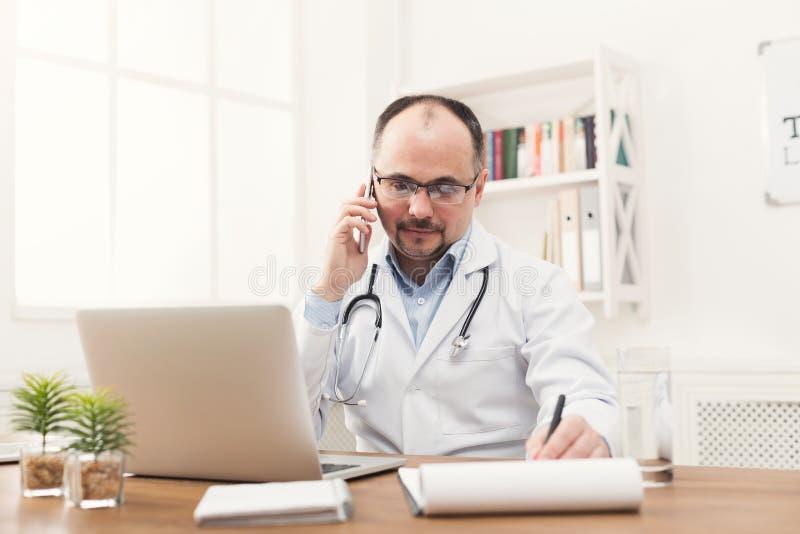 Gelukkige arts die op telefoon met zijn patiënt spreken stock afbeeldingen