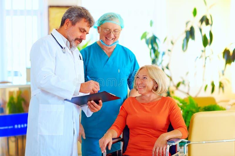 Gelukkige arts en chirurg raadplegende patiënt over behandeling alvorens van het ziekenhuis te lossen stock afbeelding