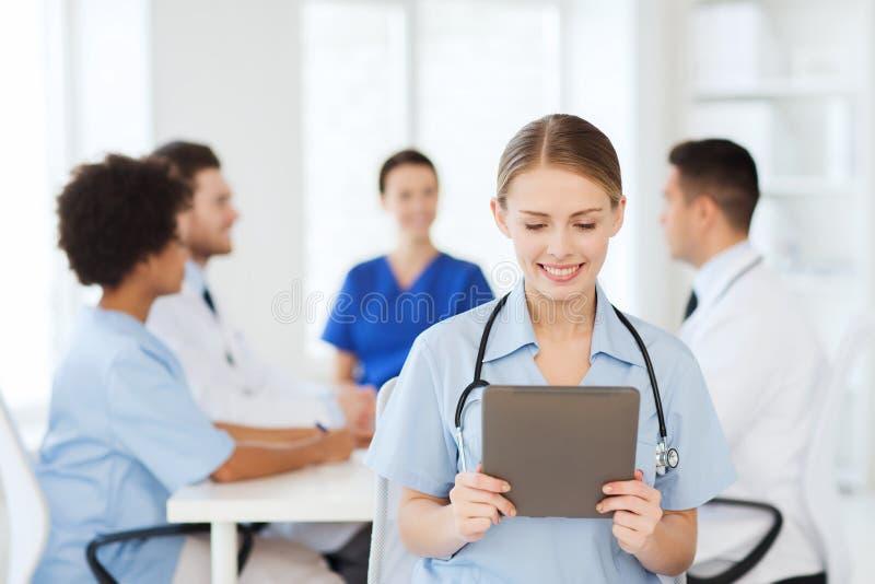 Gelukkige arts met tabletpc over team bij kliniek royalty-vrije stock afbeelding