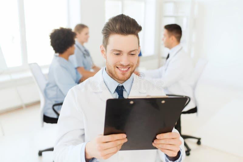 Gelukkige arts met tabletpc over team bij kliniek stock afbeelding