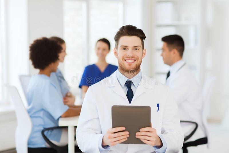 Gelukkige arts met tabletpc over team bij kliniek royalty-vrije stock foto's