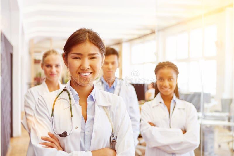 Gelukkige arts met team van verpleegsters stock foto
