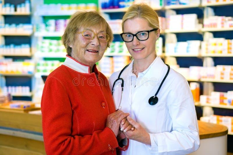 Gelukkige arts met vrouwelijke patiënt in apotheek royalty-vrije stock foto's