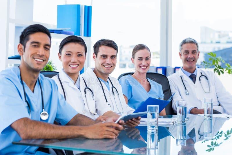 Gelukkige artsen die camera bekijken terwijl het zitten bij een lijst stock foto's