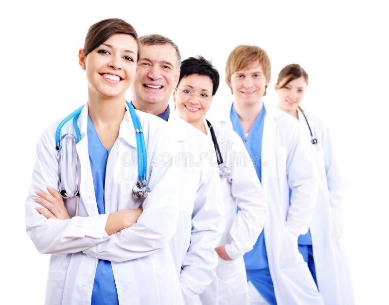 Gelukkige artsen in het ziekenhuistoga's in rij royalty-vrije stock afbeelding
