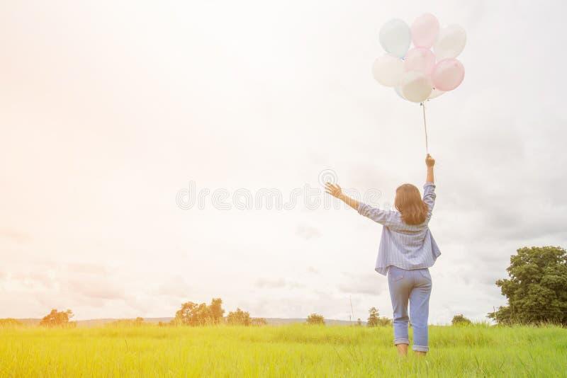 Gelukkige asin mooie vrouw met kleurrijke ballons royalty-vrije stock afbeeldingen
