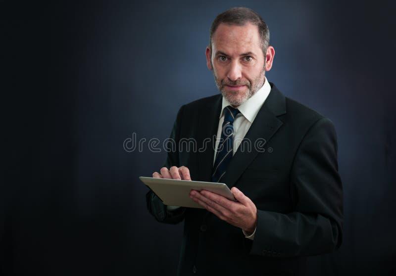 Gelukkige aturezakenman die met tablet werken royalty-vrije stock afbeelding