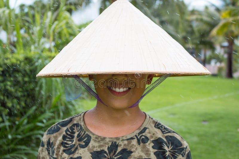 Gelukkige Aziaat met Chinese Vietnamese hoed dragen en Nieuwjaargroeten die, geen ogen is zichtbaar glimlachen stock foto's
