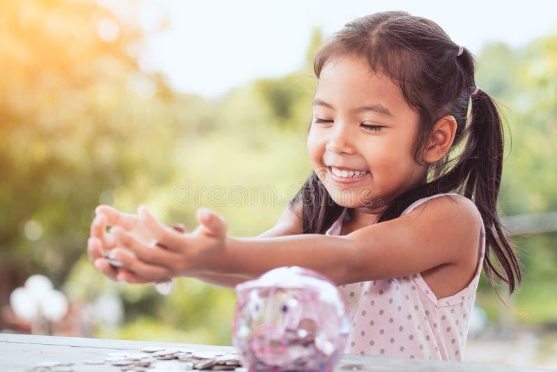 Gelukkige Aziaat weinig kindmeisje die haar geld tonen stock foto's