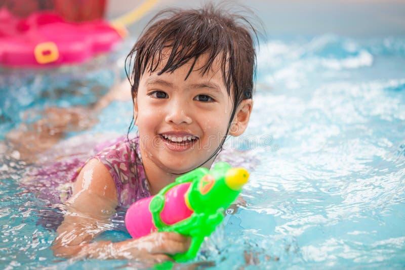 Gelukkige Aziaat weinig kindmeisje die pret hebben om waterkanon te spelen stock afbeeldingen