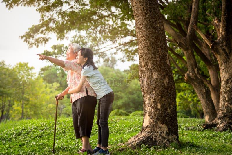 Gelukkige Aziaat weinig steun van het kindmeisje, omhelzings hogere grootmoeder, glimlachende kleindochter in openluchtpark, beja stock afbeelding