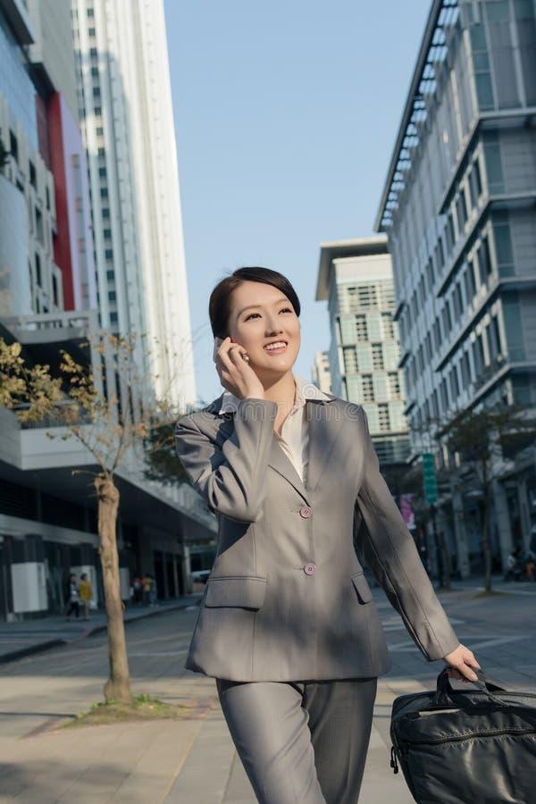 Gelukkige Aziatische bedrijfsvrouw die op telefoon spreken en op stree lopen royalty-vrije stock afbeeldingen