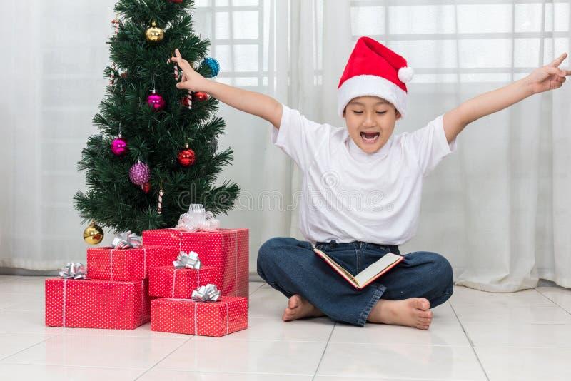 Gelukkige Aziatische Chinees weinig boek van de jongenslezing naast Kerstmis pre stock afbeelding