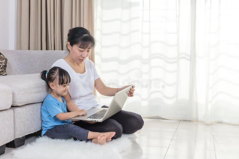 Gelukkige Aziatische Chinese moeder en dochter die laptop thuis met behulp van stock foto's
