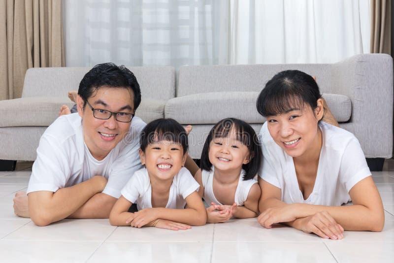 Gelukkige Aziatische Chinese ouders en dochters die op de vloer liggen stock fotografie