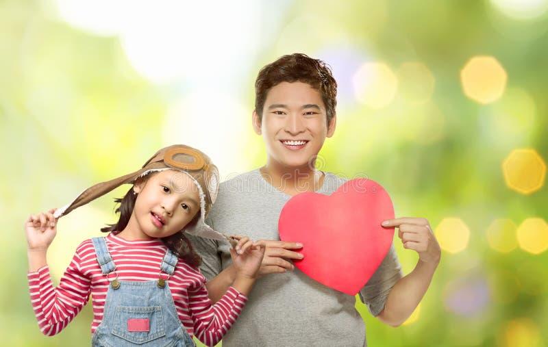 Gelukkige Aziatische dochter en haar vader die rood hart houden royalty-vrije stock foto's