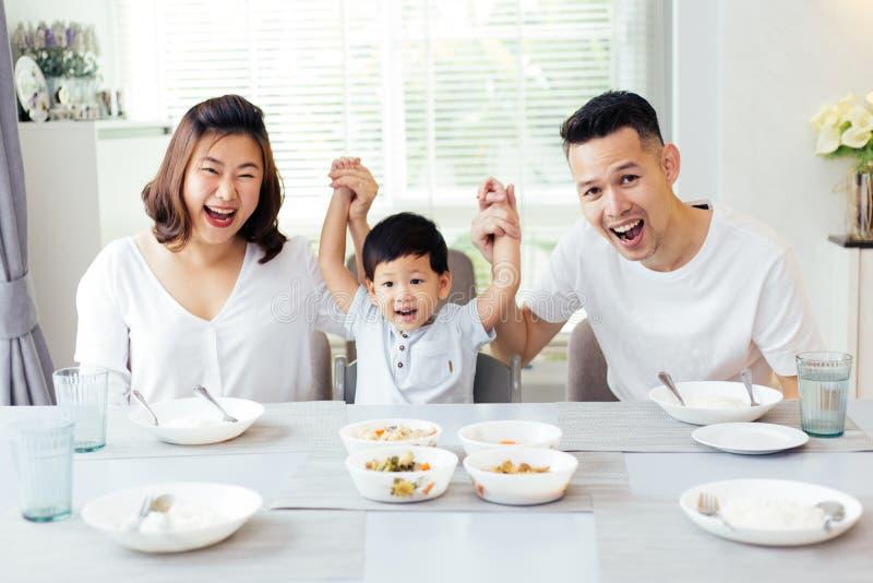Gelukkige Aziatische familie die kind` s handen opheffen omhoog en terwijl het hebben van een maaltijd samen glimlachen royalty-vrije stock fotografie