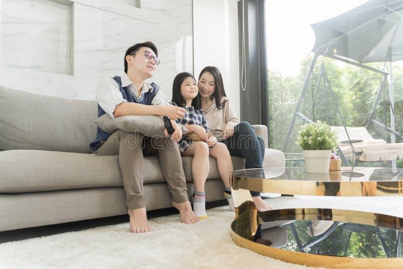 Gelukkige Aziatische familie die op TV samen op bank in woonkamer letten Familie en huisconcept stock afbeeldingen