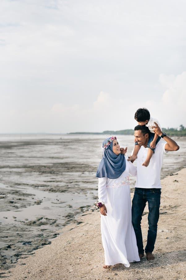 Gelukkige Aziatische familie die prettijd hebben samen bij het modderige die strand in Pantai Remis, Kuala Selangor, Selangor, Ma royalty-vrije stock foto's