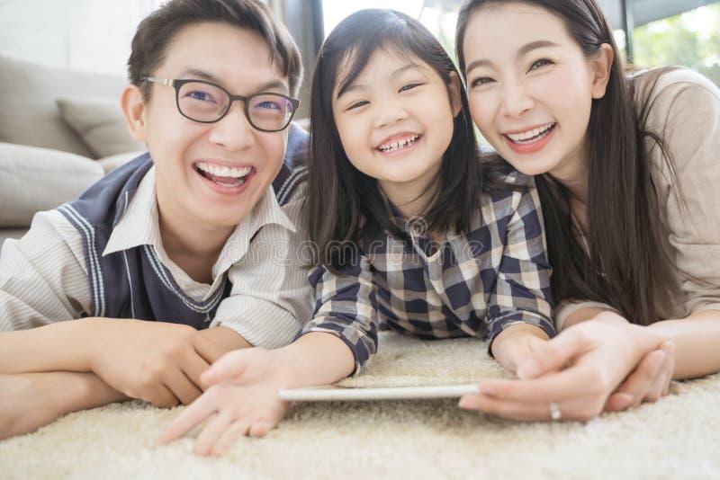 Gelukkige Aziatische familie het besteden tijd samen op bank in woonkamer Familie en huisconcept stock foto