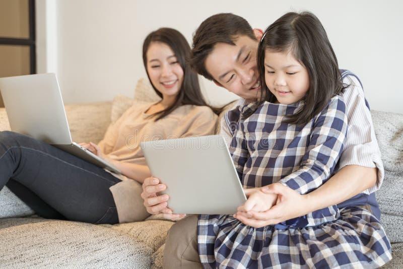 Gelukkige Aziatische familie het besteden tijd samen op bank in woonkamer Familie en huisconcept royalty-vrije stock foto's
