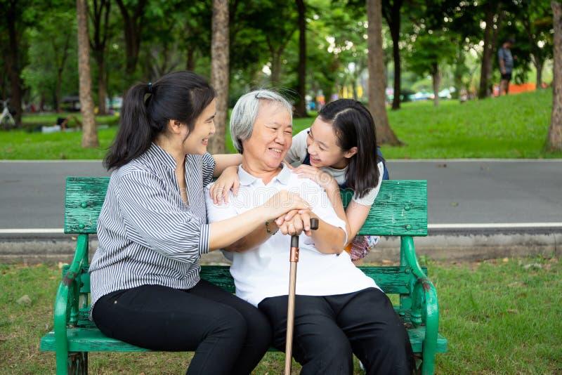 Gelukkige Aziatische familie in openluchtpark, het glimlachen hogere vrouwenzitting op een bank terwijl haar dochter en kleindoch royalty-vrije stock afbeelding
