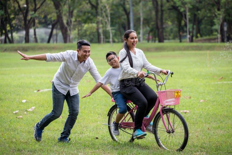 gelukkige Aziatische Familie, ouders en hun kinderen die fiets in park samen berijden de vader duwt moeder en zoon op fiets die p stock foto's