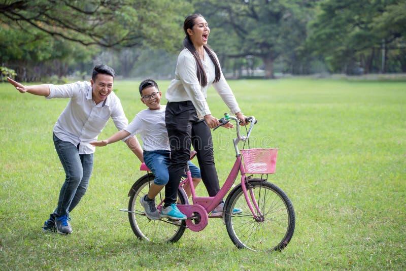 gelukkige Aziatische Familie, ouders en hun kinderen die fiets in park samen berijden de vader duwt moeder en zoon op fiets die p royalty-vrije stock afbeeldingen
