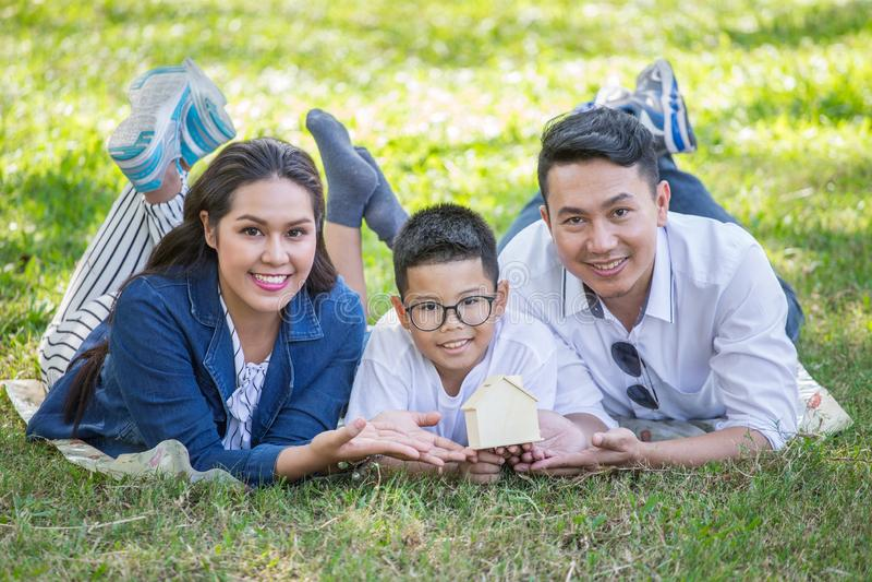 gelukkige Aziatische Familie, ouders en hun kinderen die op gras in park liggen die camera samen bekijken Vader, moeder en zoon royalty-vrije stock afbeelding