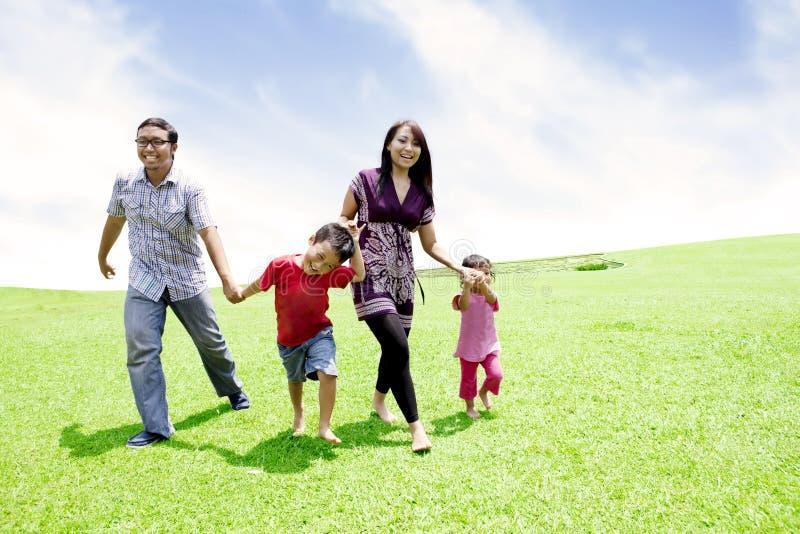Gelukkige Aziatische familie in weide stock afbeeldingen