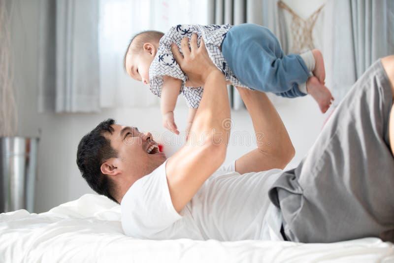 Gelukkige Aziatische familievader met babyzoon het spelen op bed met smil royalty-vrije stock afbeelding
