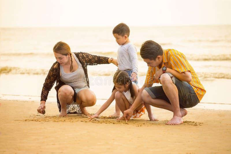 Gelukkige Aziatische familiezitting op de strandtekening in het zand die samen van zonsondergang in de de zomervrije tijd geniete stock foto