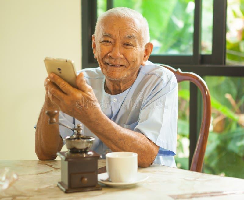 Gelukkige Aziatische hogere mens die de mobiele telefoon met behulp van stock afbeeldingen