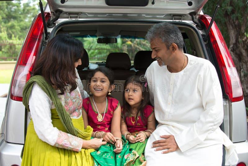 Gelukkige Aziatische Indische familiezitting in auto het spreken stock afbeeldingen