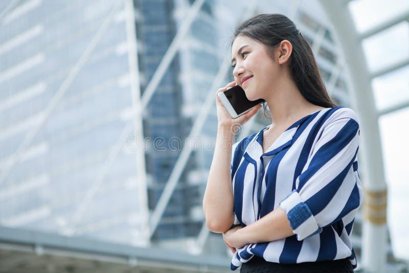 Gelukkige Aziatische jonge bedrijfsvrouw die op mobiele telefoon in stad spreken openlucht stock fotografie