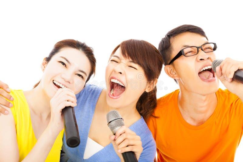 Gelukkige Aziatische jonge groep die pret het zingen met karaoke hebben stock foto's