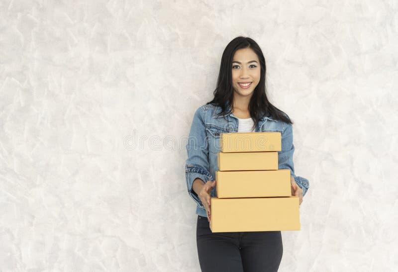 Gelukkige Aziatische jonge leveringsvrouw die zich met pakketpostdoos bevinden op witte achtergrond royalty-vrije stock afbeeldingen