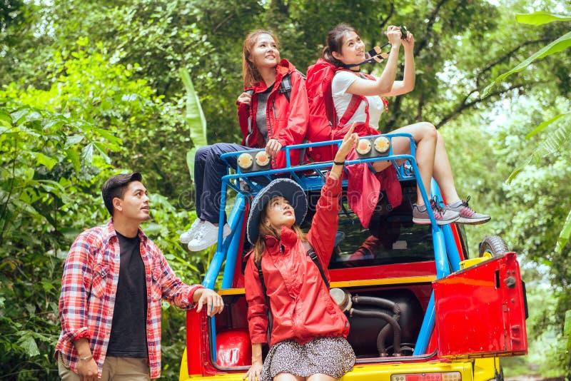 Gelukkige Aziatische jonge reizigers met 4WD aandrijvingsauto van weg in bos royalty-vrije stock afbeelding