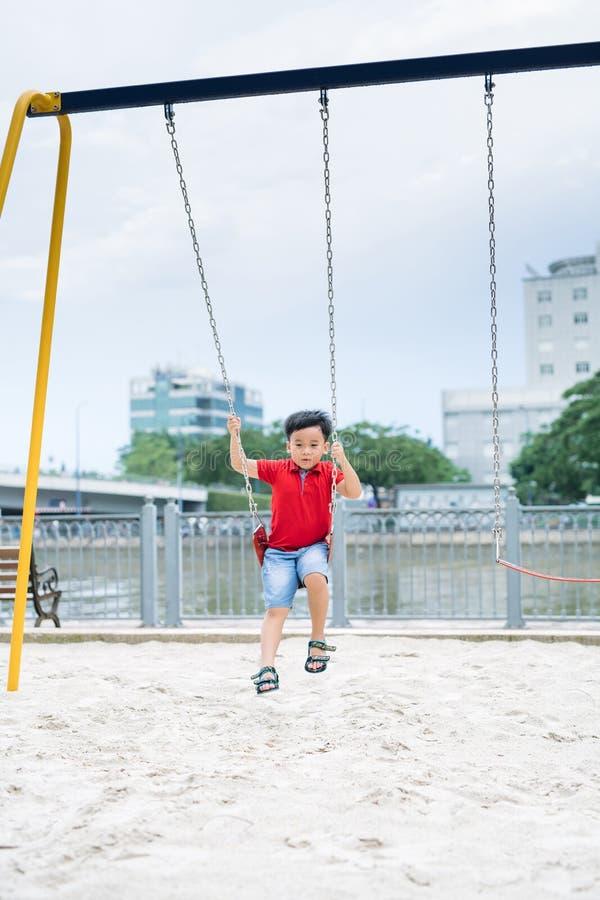 Gelukkige Aziatische jongen die bij de speelplaats in het park slingeren royalty-vrije stock foto's