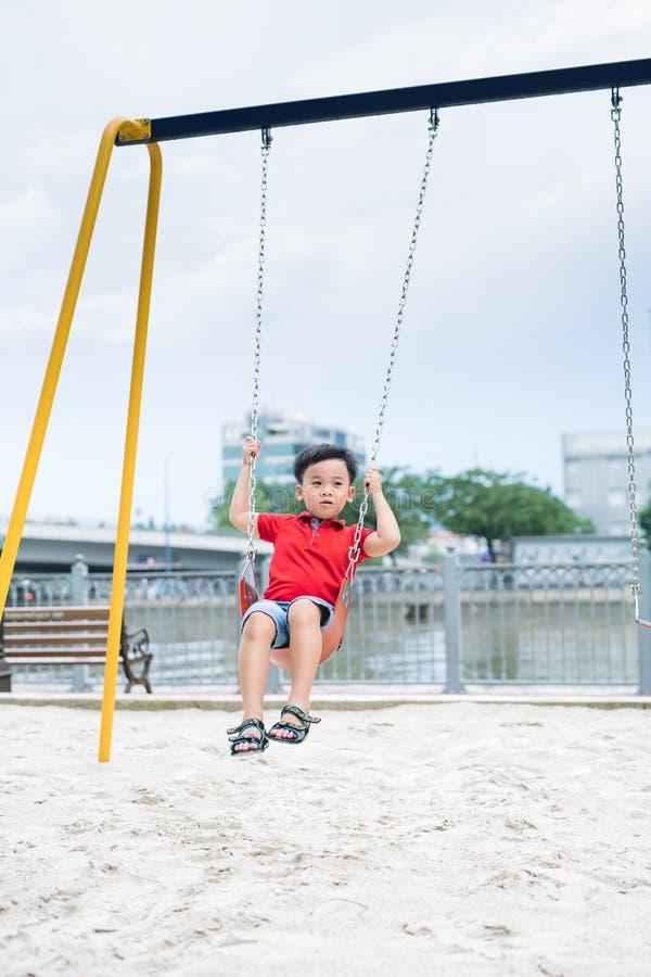 Gelukkige Aziatische jongen die bij de speelplaats in het park slingeren stock foto