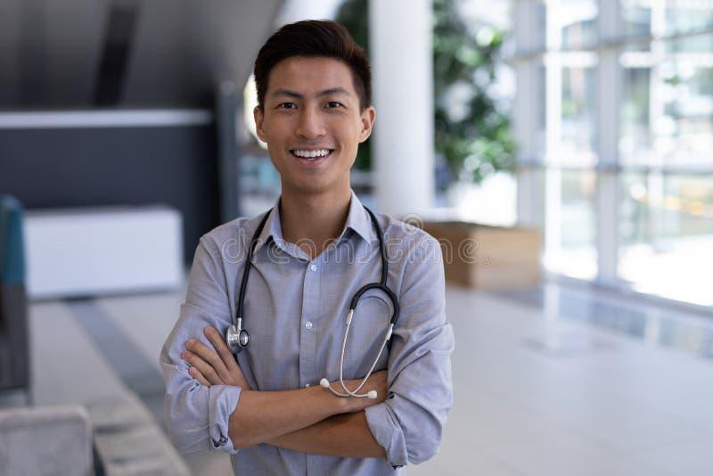 Gelukkige Aziatische mannelijke arts die zich met wapens bevinden die in het ziekenhuis worden gekruist stock foto