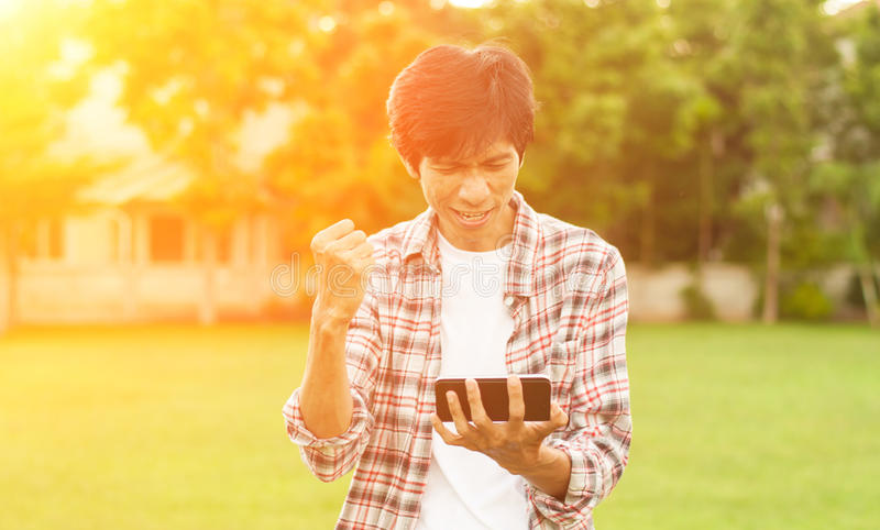 Gelukkige Aziatische mens met nieuws of bericht van slimme telefoon in tuin, stock afbeeldingen