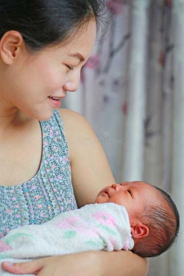 Gelukkige Aziatische moeder die haar baby op haar borst vervoeren stock foto's
