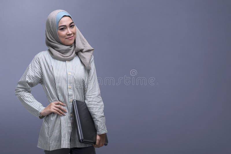 Gelukkige Aziatische moslimvrouw die laptop van de sluierholding dragen stock afbeeldingen