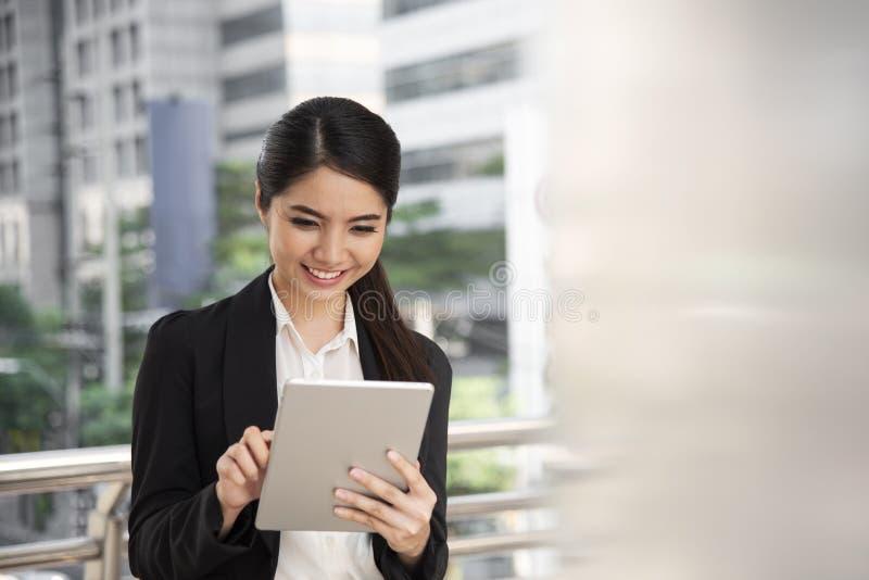 Gelukkige Aziatische onderneemster die digitale tabletcomputer met behulp van stock foto
