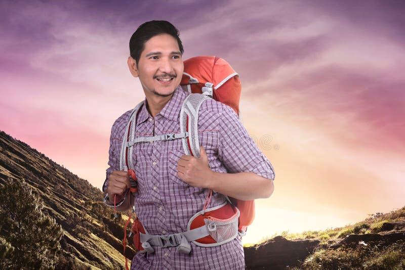 Gelukkige Aziatische toeristenmens met rugzak het beklimmen royalty-vrije stock foto's