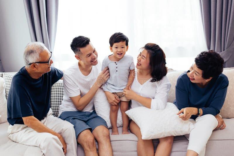 Gelukkige Aziatische uitgebreide familiezitting op bank die samen, voor groepsfoto's stellen stock foto's