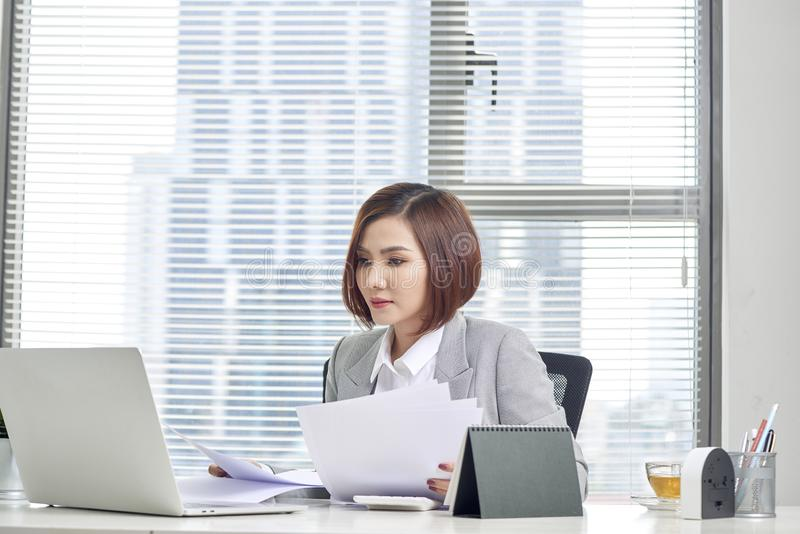 Gelukkige Aziatische vrouw die in bureau werken Wijfje die door wat administratie op het werkplaats gaan stock foto