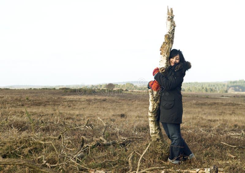 Gelukkige Aziatische vrouw die een boom koestert royalty-vrije stock fotografie