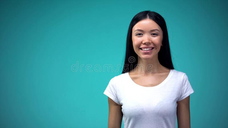 Gelukkige Aziatische vrouw die en camera, perfecte huidhaar en tanden glimlachen bekijken royalty-vrije stock foto's